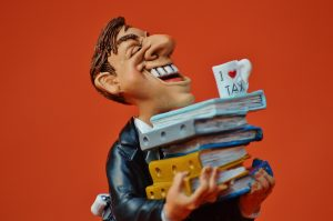 Cartoonish picture of a man balancing an I love Tax mug on top of a pile of files.